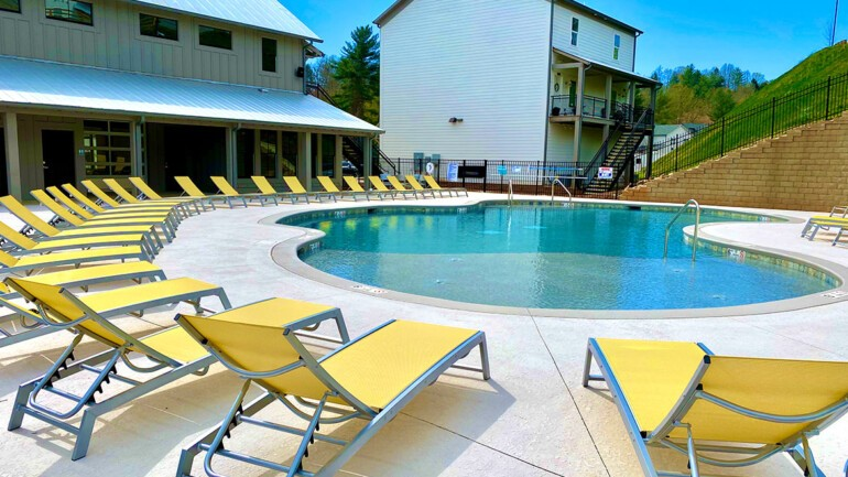 Another image of the pool with bright yellow lounge chairs around it.